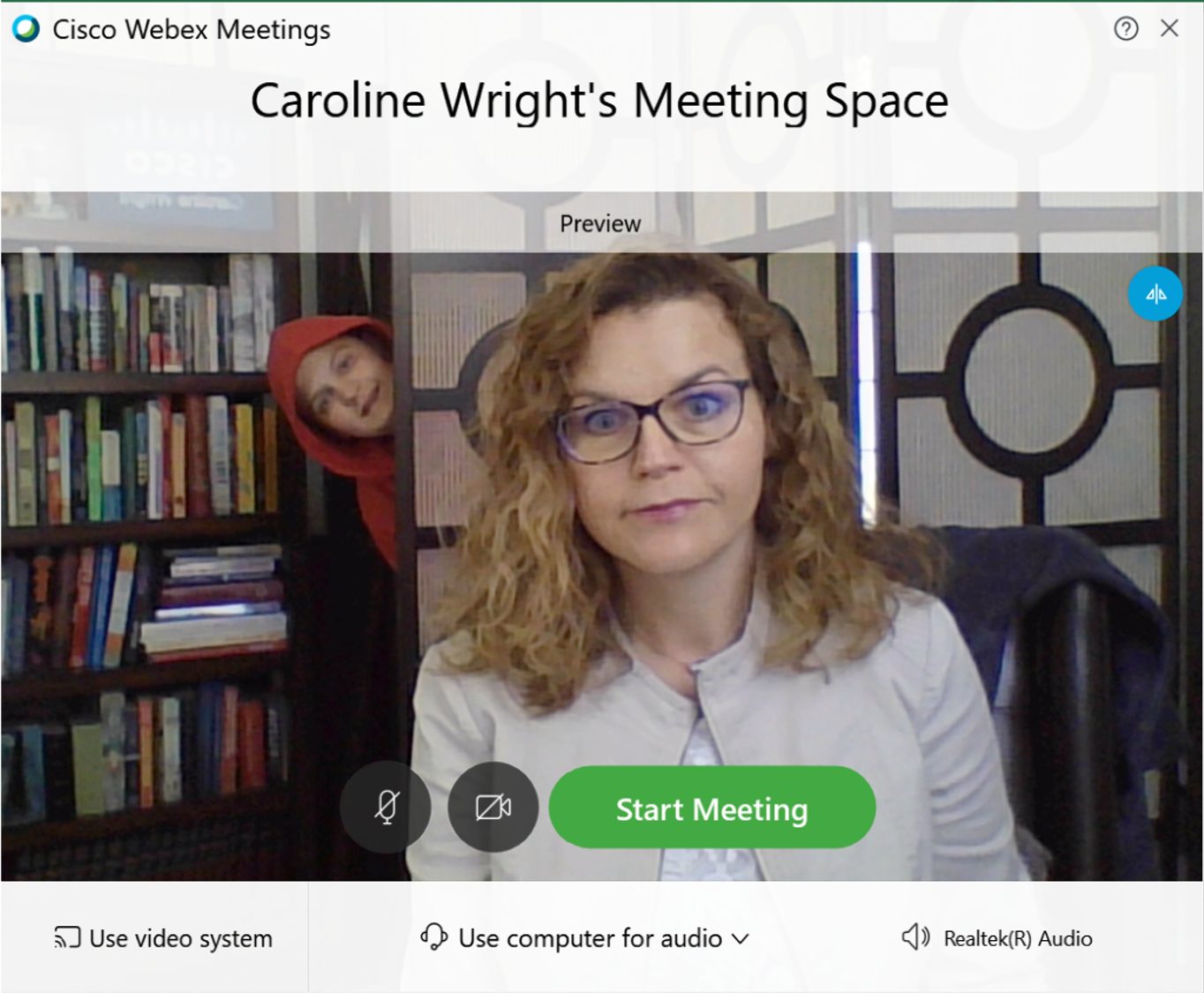 CarolineWright'ssonphotobombinghermeeting. Son peaking in from behind the door wearing red hoodie while Caroline wearing a white dress jacket and black glasses sees reflection and shows a smirk